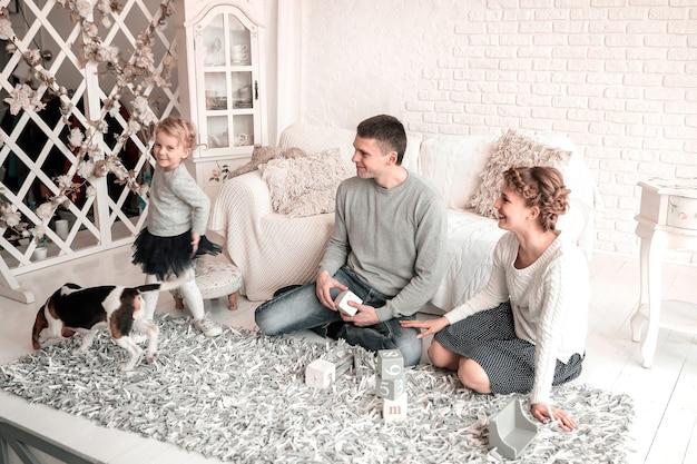 Eltern mit einer kleinen tochter und einem haustier, die auf der couch sitzen.
