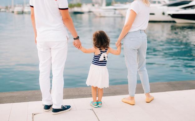 Eltern mit einer tochter am meer. vater und mutter halten das baby an der hand.
