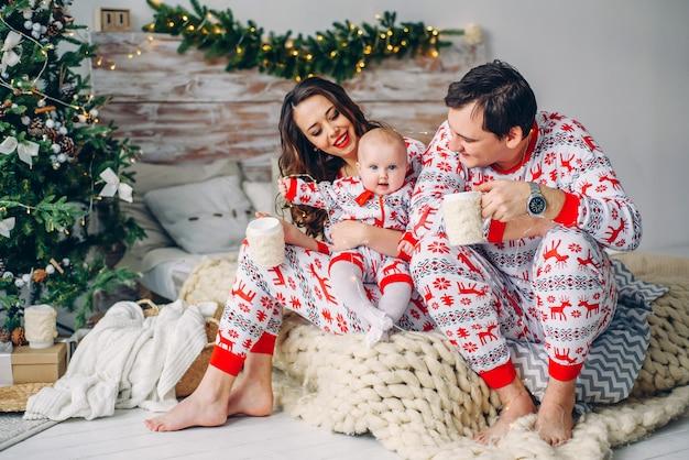 Eltern mit ihrer kleinen tochter in der feiertagskleidung mit den gedruckten rotwild und schneeflocken, die auf dem bett mit tassen tee im gemütlichen raum sitzen