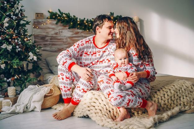 Eltern mit ihrer kleinen tochter in der feiertagskleidung mit den gedruckten rotwild und schneeflocken, die auf dem bett sitzen