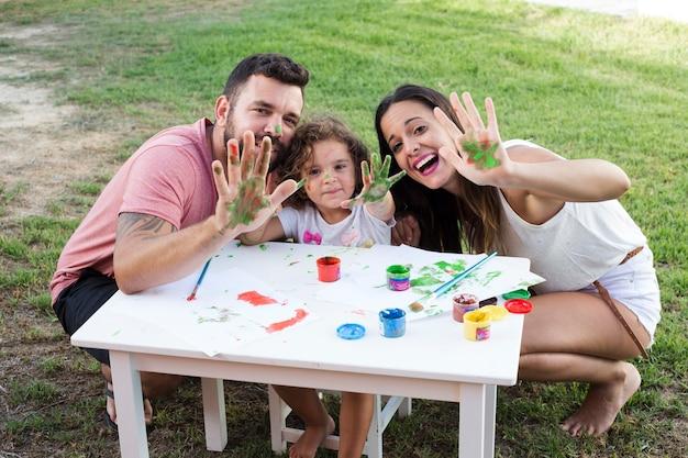 Eltern mit ihrer tochter, die ihre unordentlichen hände beim malen im park zeigt