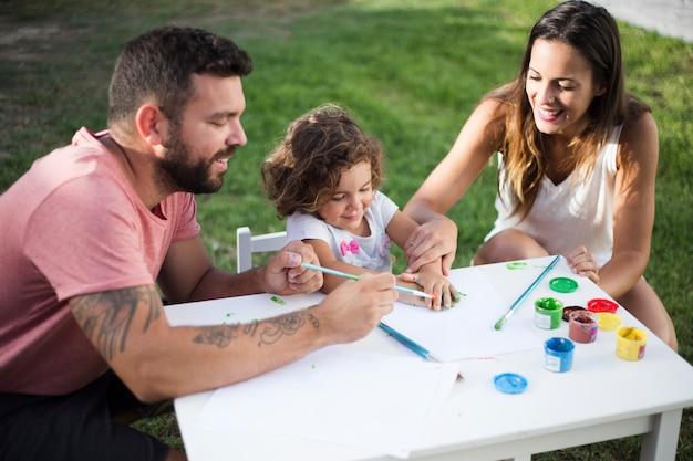 Eltern mit ihrer tochter, die zusammen im park malt