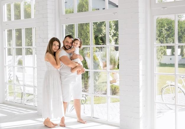 Eltern mit ihrer tochter in ihrer wohnung mit großen fenstern. familientag zu hause. ein großer weißer raum mit raumhohen fenstern.