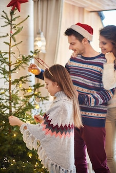 Eltern mit kind hängen weihnachtsdekoration