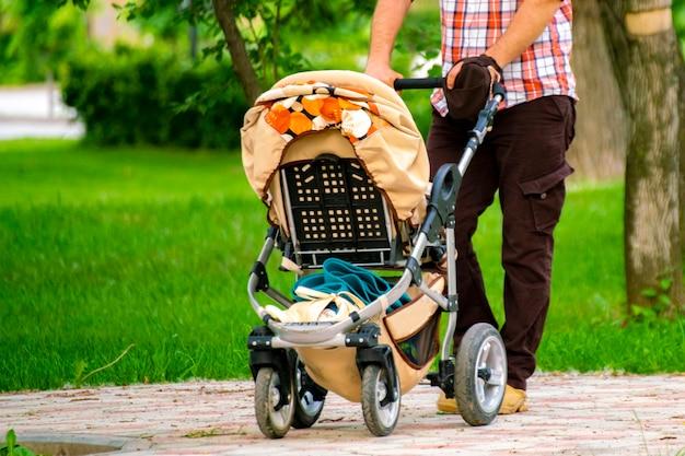 Eltern mit kinderwagen, die im freien in den öffentlichen parkgassen der stadtstraße spazieren gehen
