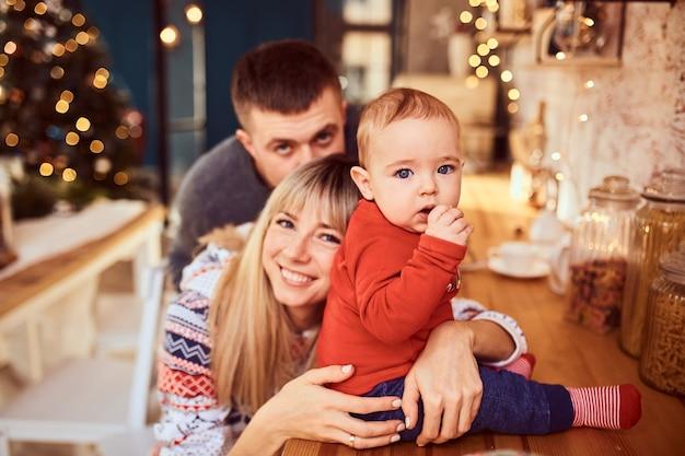 Eltern mit seinem entzückenden sohn auf einem weihnachtsfotoshooting