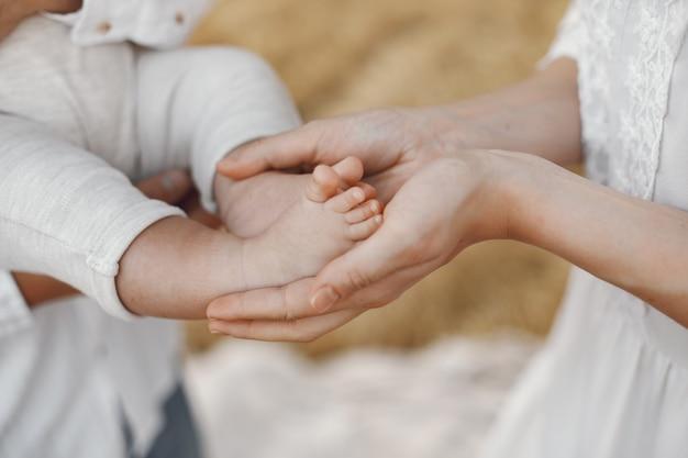 Eltern mit tochter. familie auf einem feld. neugeborenes mädchen. frau in einem weißen kleid.