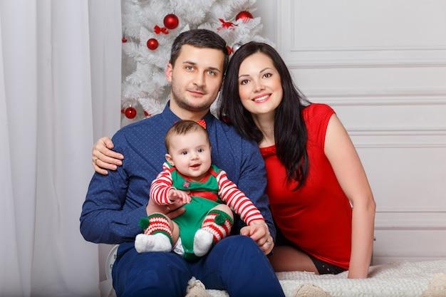 Eltern mit tochter in einer weihnachtsfotosession