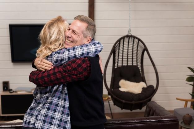 Eltern posieren, während sie umarmt werden