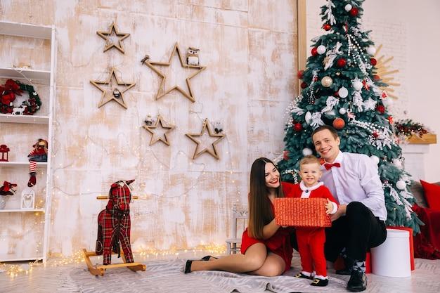 Eltern sitzen in der nähe von weihnachtsbaum. baby in santa kostüm gemütlichen raum mit spielzeug.