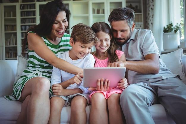 Eltern sitzen mit ihren kindern auf dem sofa und benutzen ein digitales tablet im wohnzimmer