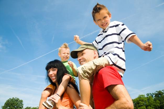 Eltern tragen ihre kinder auf den schultern