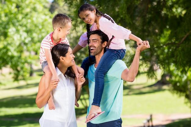 Eltern tragen ihre kinder auf der schulter im park