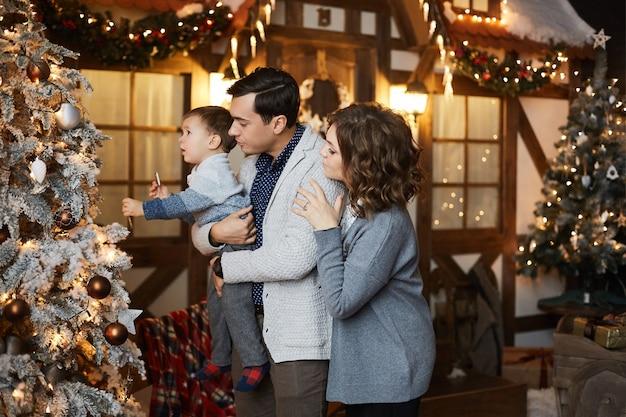 Eltern und ihr kleiner sohn haben spaß an weihnachten