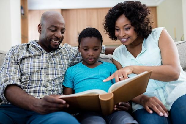 Eltern und ihr sohn betrachten fotoalbum im wohnzimmer