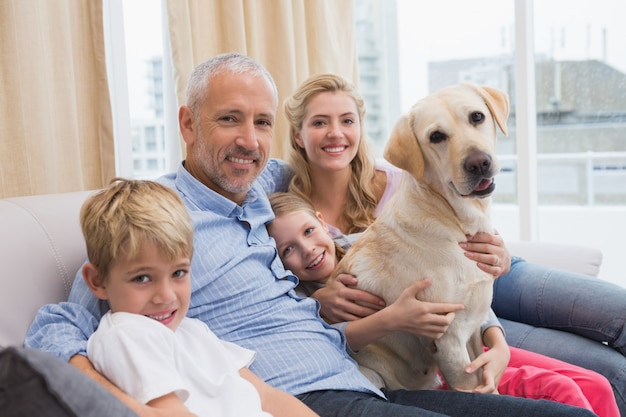 Eltern und ihre kinder auf sofa mit labrador