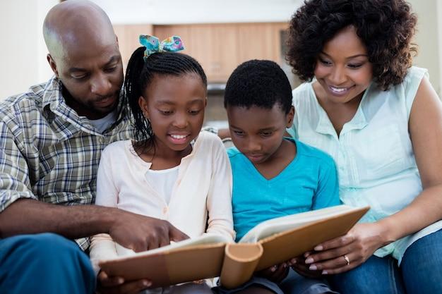 Eltern und ihre kinder betrachten fotoalbum im wohnzimmer