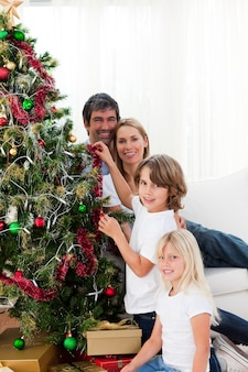 Eltern und ihre kinder schmücken einen weihnachtsbaum