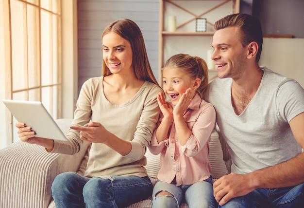 Eltern und ihre kleine tochter, die eine digitale tablette verwenden