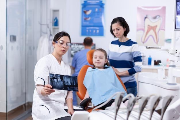 Eltern und kind in der zahnarztpraxis, die sich die vom zahnarzt durchgeführte zahnärztliche radiographie ansehen. stomatologe, der mutter des kindes in der gesundheitsklinik mit röntgenaufnahme die zahndiagnose erklärt.