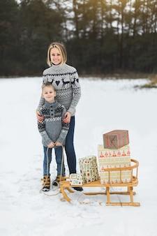 Eltern und kind mit schlitten, winterrodeln, outdoor-aktivitäten