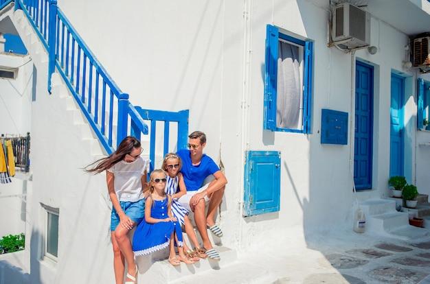 Eltern und kinder an der straße des typischen griechischen traditionellen dorfs