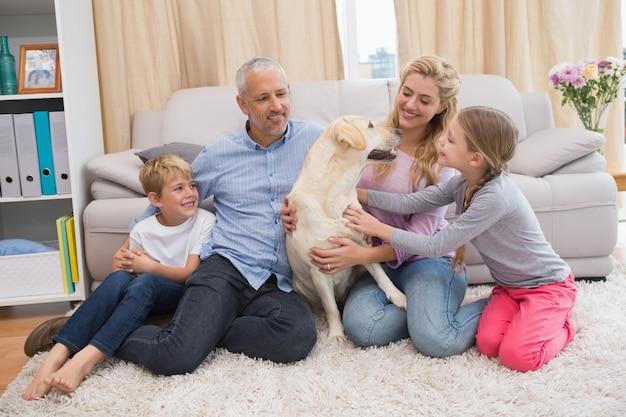 Eltern und kinder auf teppich mit labrador