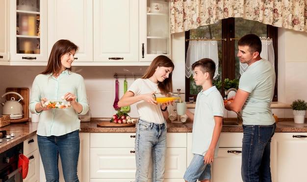 Eltern und kinder bereiten essen in der küche zu