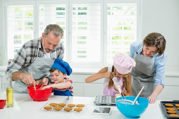 Eltern und kinder bereiten kekse in der küche vor