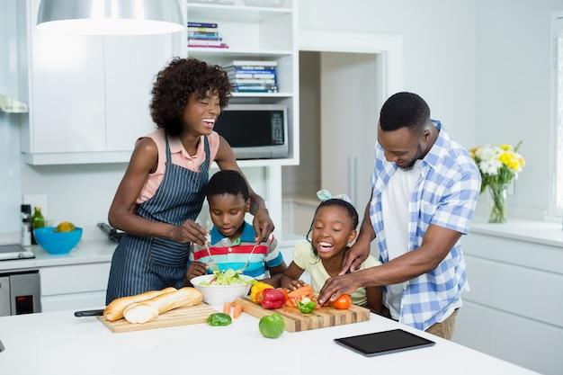Eltern und kinder bereiten salat in der küche zu
