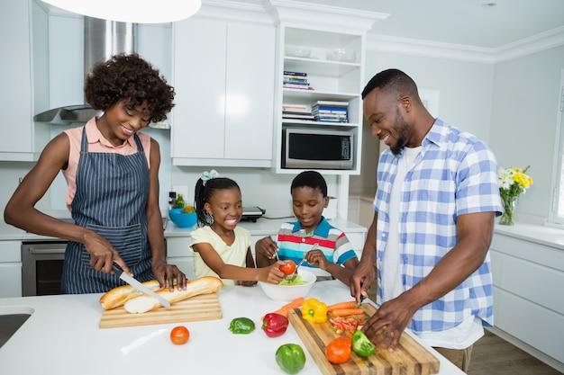 Eltern und kinder bereiten salat vor, während vater digitales tablett in der küche verwendet
