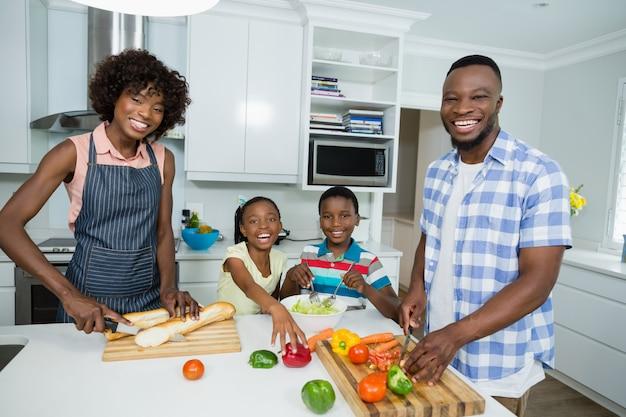 Eltern und kinder bereiten salat vor, während vater digitales tablett in der küche zu hause verwendet