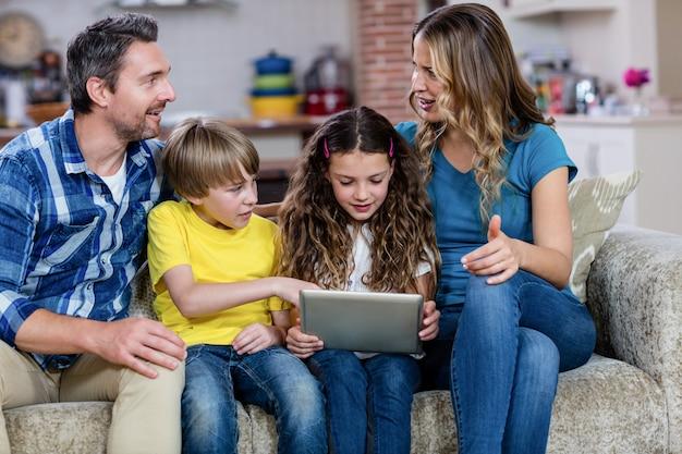 Eltern und kinder, die auf sofa sitzen und eine digitale tablette verwenden