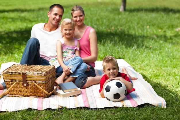 Eltern und kinder, die bei einem picknick sich entspannen