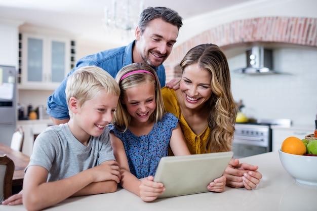 Eltern und kinder, die digitale tablette in der küche verwenden