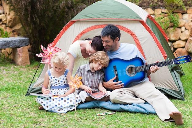 Eltern und kinder, die eine gitarre in einem zelt spielen