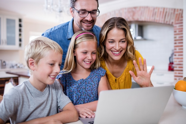 Eltern und kinder, die laptop in der küche verwenden