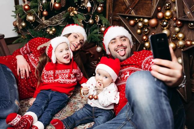 Eltern und kinder, die selfie bei chrisrmas nehmen