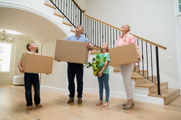 Eltern und kinder halten pappkartons im wohnzimmer zu hause