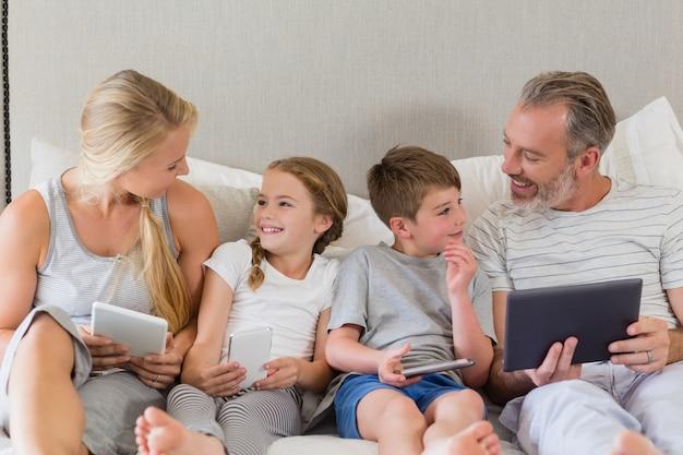 Eltern und kinder interagieren, während sie das digitale tablet auf dem bett verwenden