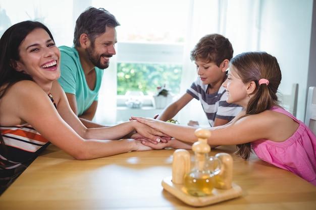 Eltern und kinder legen ihre hände zusammen auf den tisch