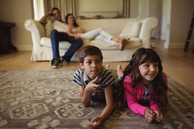 Eltern und kinder sehen im wohnzimmer fern