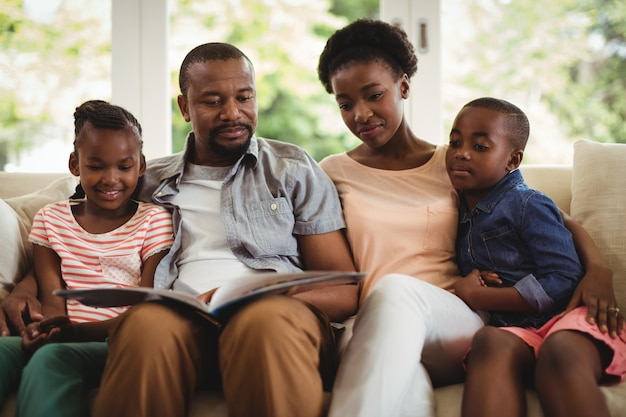Eltern und kinder sitzen zusammen auf sofa mit fotoalbum