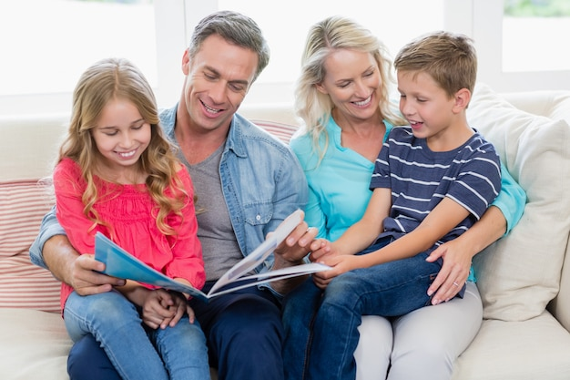 Eltern und kinder sitzen zusammen auf sofa und betrachten fotoalbum