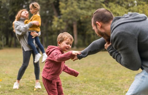 Eltern und kinder spielen draußen zusammen