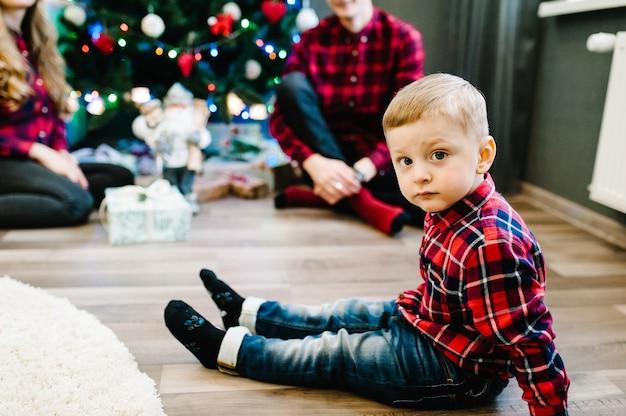 Eltern und kleine kinder in der nähe von weihnachtsbaum drinnen. weihnachtsfamilie geben geschenkgeschenkbox, nacht weihnachten. frohe weihnachten und schöne feiertage! familie, die geschenke austauscht.