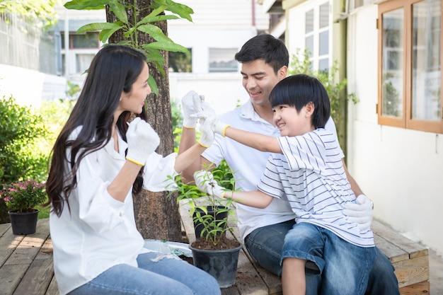 Eltern und kleiner sohn pflanzen einen baum in topf