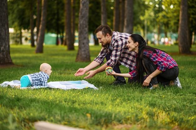 Eltern und kleines baby spielen auf gras im sommerpark