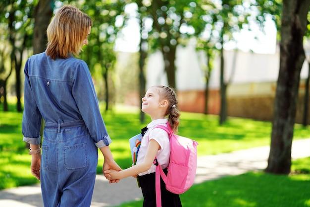 Eltern und schüler der grundschule gehen hand in hand. frau und mädchen mit rucksack hinter dem rücken. beginn des unterrichts. erster tag im herbst