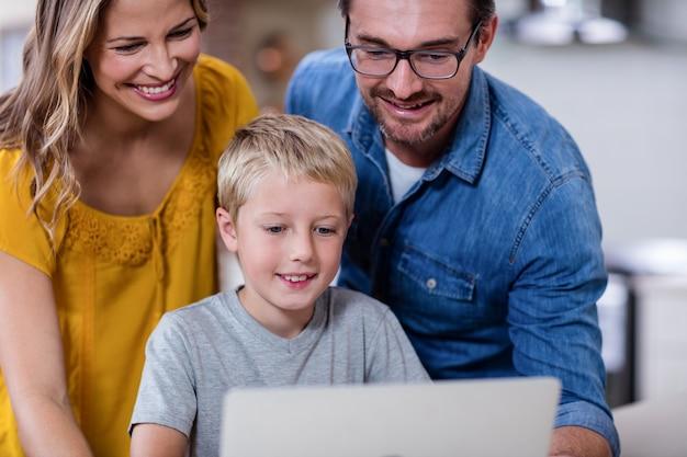 Eltern und sohn, der laptop in der küche verwendet